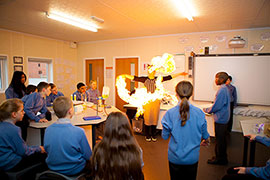 Students gathered around for a fiery science demo in chemistry